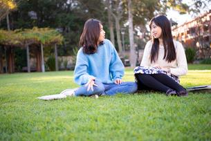 芝生に座って話している2人の写真素材 [FYI01706066]