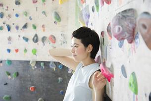 ボルダリングの壁に寄り掛かる女性の写真素材 [FYI01706071]
