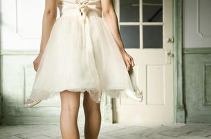 靴を脱いだドレス姿の女性の後ろ姿の写真素材 [FYI01706088]