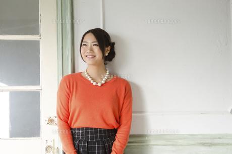 壁の前で笑う女性の写真素材 [FYI01706094]
