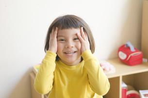 顔に手を当てている女の子の写真素材 [FYI01706105]