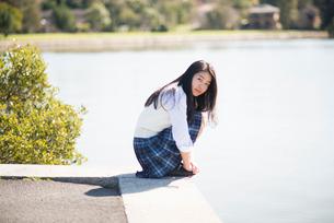 水辺で座っている制服姿の女子高生の写真素材 [FYI01706109]