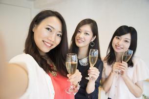 シャンパンを持って自撮りをしている女性たちの写真素材 [FYI01706116]