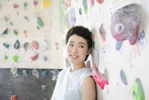 ボルダリングの壁の前で笑う女性の写真素材 [FYI01706128]