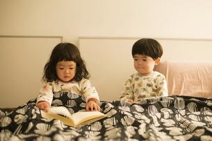 ベッドで本を広げている双子の写真素材 [FYI01706133]