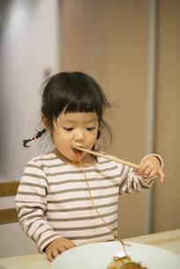 お箸で焼きそばを食べている女の子の写真素材 [FYI01706137]