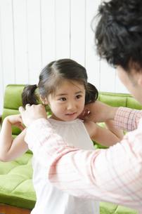 父親にお着替えを手伝ってもらっている女の子の写真素材 [FYI01706147]