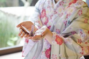手のひらに折り鶴を置いた着物姿の女性の写真素材 [FYI01706196]