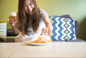 部屋でポテトチップをつまんでいる女性の写真素材 [FYI01706202]