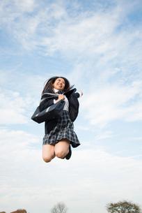 ジャンプをしている制服姿の女子高生の写真素材 [FYI01706206]