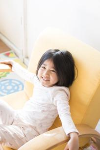 パジャマ姿でソファに座る女の子の写真素材 [FYI01706244]