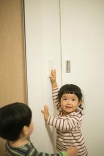 照明のスイッチを消そうとしている女の子の写真素材 [FYI01706253]