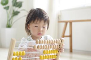 部屋の中で100玉そろばんで遊ぶ女の子の写真素材 [FYI01706269]