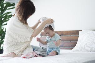 ベッドの上で着替えをする男の子とお母さんの写真素材 [FYI01706275]