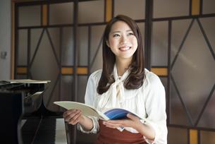 ピアノの前で楽譜を持っている女性の写真素材 [FYI01706302]