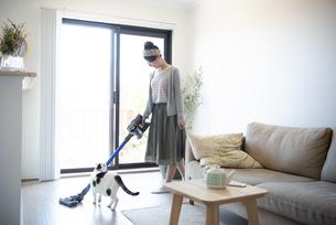 リビングで掃除機をかけている女性と猫の写真素材 [FYI01706310]