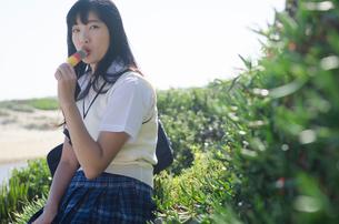 カラフルなアイスを食べる制服姿の女の子の写真素材 [FYI01706371]