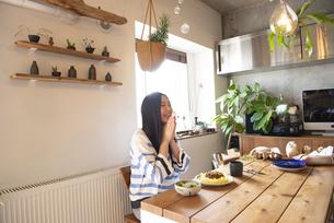 テーブルでご飯を食べようとしている女性の写真素材 [FYI01706376]