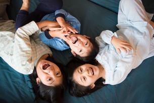 ベッドに寝転がっている子供達の写真素材 [FYI01706382]