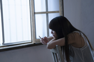 イスに座ってスマートフォンを操作する女性の写真素材 [FYI01706397]