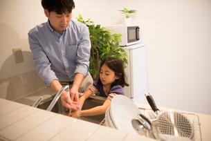 お皿を洗っている女の子と父親の写真素材 [FYI01706399]