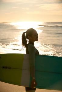 サーフボードを抱えているウェットスーツ姿の女性の写真素材 [FYI01706401]