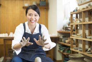 陶芸教室で手を広げている女性の写真素材 [FYI01706417]