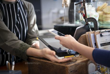お店でスマホを使って電子決済をしている女性の写真素材 [FYI01706419]