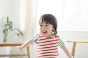 両手を広げて笑っている男の子の写真素材 [FYI01706428]
