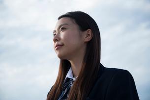 遠くを見ている制服姿の女子高生の写真素材 [FYI01706435]