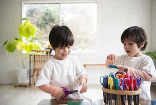 ハサミで遊んでいる双子兄弟の写真素材 [FYI01706449]