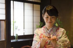 手のひらに折り鶴を乗せた着物姿の女性の写真素材 [FYI01706454]