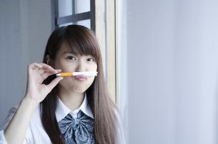 ペンを鼻の下に挟む制服姿の女性の写真素材 [FYI01706466]