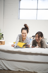 ベッドの上で話している女性2人の写真素材 [FYI01706494]