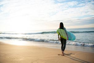 サーフボードを抱えて砂浜を歩いている女性の写真素材 [FYI01706496]