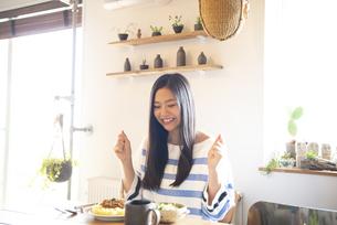 テーブルでご飯を食べようとしている女性の写真素材 [FYI01706516]