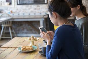 カフェでスマホを使ってスイーツの写真を撮っている女性の写真素材 [FYI01706517]