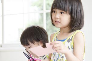 紙を切っている女の子と男の子の写真素材 [FYI01706520]