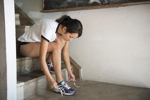 スニーカーの靴紐を結んでいる女性の写真素材 [FYI01706521]