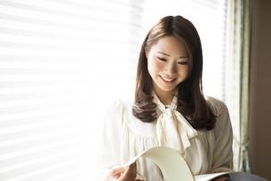 窓辺で楽譜を持っている女性の写真素材 [FYI01706525]