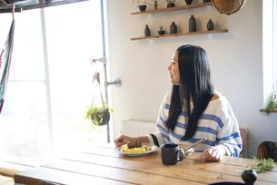 テーブルで横を向いている女性の写真素材 [FYI01706526]