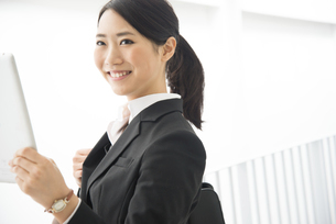 タブレットを持っているスーツ姿の女性の写真素材 [FYI01706539]