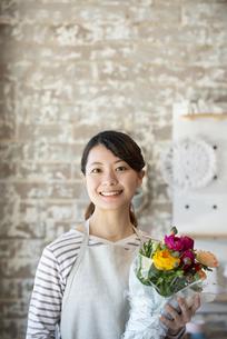 花束を持っている笑顔の店員の女性の写真素材 [FYI01706572]