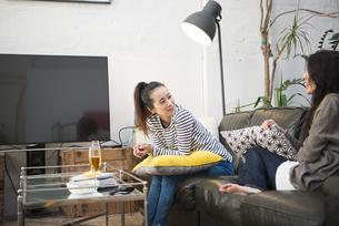 ソファに座っておしゃべりをしている女性2人の写真素材 [FYI01706582]
