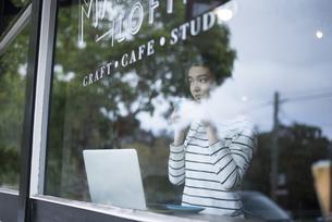 カフェでパソコンを開いてる窓ガラス越しの女性の写真素材 [FYI01706595]