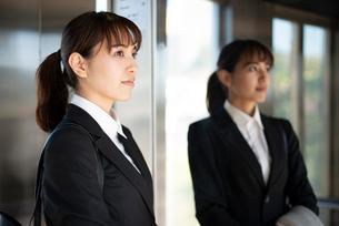 スーツを着てエレベーターに乗っている女性の写真素材 [FYI01706618]
