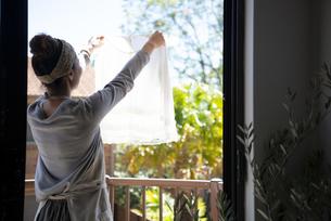洗濯物の白い服を広げている女性の写真素材 [FYI01706668]