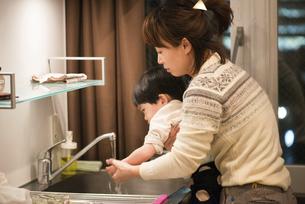 台所で手を洗っている男の子と母親の写真素材 [FYI01706684]