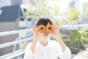 ドーナツを持っている女性の写真素材 [FYI01706692]