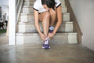 スニーカーの靴紐を結んでいる女性の写真素材 [FYI01706719]